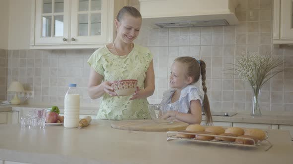 Thumbnail for Beautiful Young Mother and Little Cute Daughter Cook in the Kitchen Together