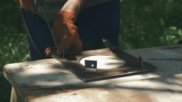 Blacksmith welder in protective mask works with metal steel and iron using welding machine.