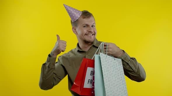 Man Raising Shopping Bags, Dancing, Celebrating, Enjoying Discounts on Black Friday Sale Holiday