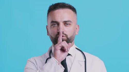 Portrait of Serious Doctor Holding Finger on Lips, Blue Studio Background