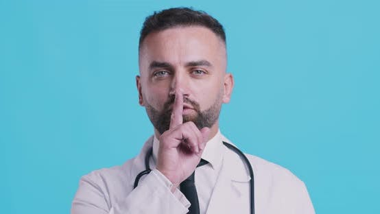 Thumbnail for Portrait of Serious Doctor Holding Finger on Lips, Blue Studio Background