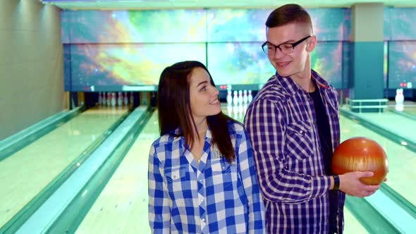 Thumbnail for Boy and Girl Look at Each Other at the Bowling