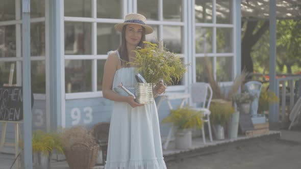 Thumbnail for Cute Young Woman in Straw Hat and White Dress Looking at the Camera Smiling While Sniffing Wild