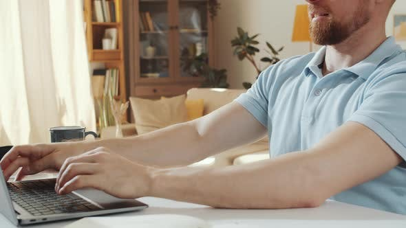 Midsection of Man Browsing the Internet on Laptop at Home