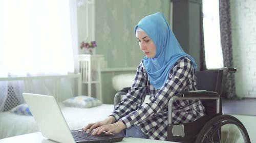 Beautiful Young Woman in Hijab Disabled Person Wheelchair Work at Computer