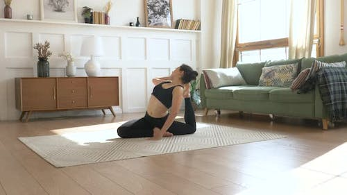 Sporty Indian Woman Doing Stretching Exercise Yoga. Black Sportswear Light Room At home
