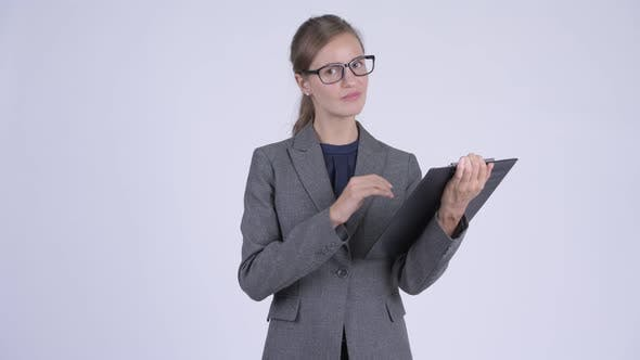 Cover Image for Young Stressed Businesswoman Giving Thumbs Down While Showing Clipboard