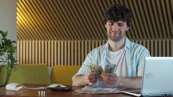 Man Counts the Money Sitting at the Table and Throws the Money Up