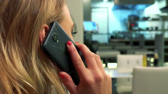Thumbnail for A Woman Sits at a Table in a Restaurant and Talks on a Smartphone - Closeup