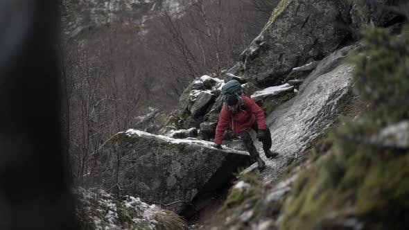 Зрелый турист делает путь вниз скользкие скалы