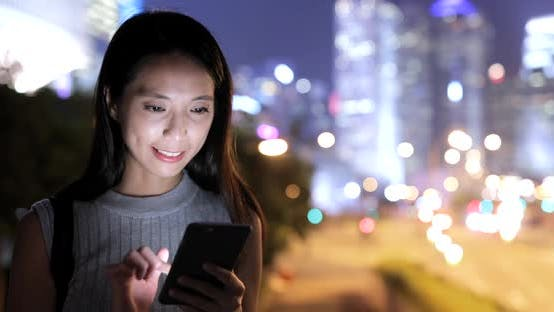 Thumbnail for Woman using mobile phone in city at night