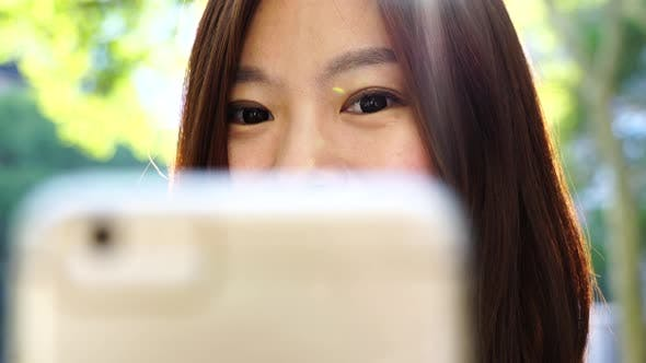 Thumbnail for Beautiful Young Asian Female Browsing the Internet on Mobil Phone