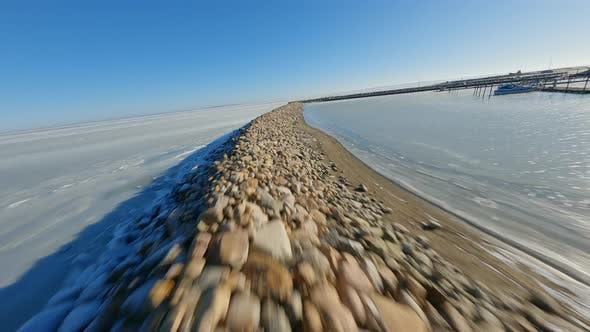 Snowy Frozen Lake FPV Drone Shot with Bright Sun