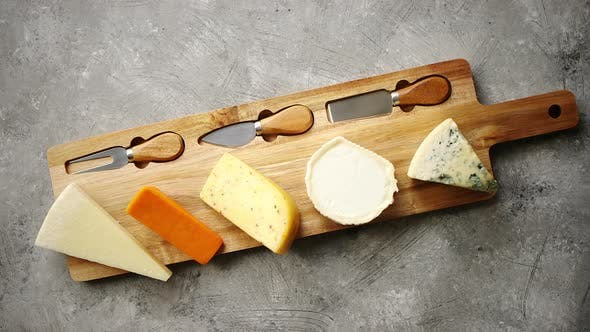 Thumbnail for Assortment of Various Kinds of Cheeses Served on Wooden Board with Fork and Knives