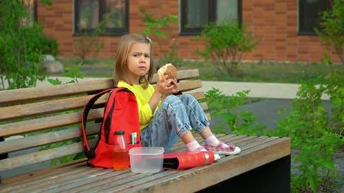 Girl Sits in Schoolyard and Eats Hamburger
