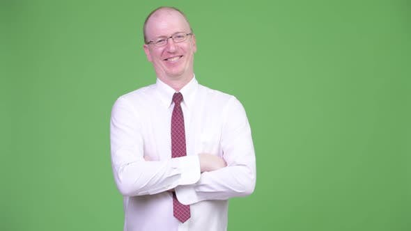 Thumbnail for Happy Mature Bald Businessman with Arms Crossed