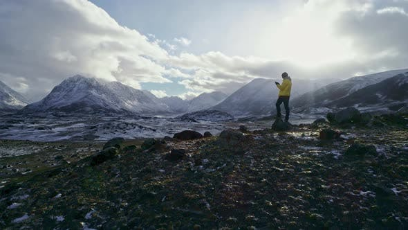 Strong Man Hiker Taking Photo with Smart Phone at Mountain Peak. Marvelous Daybreak