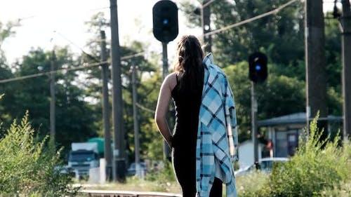 Young Beautiful Woman Walks Alone on the Railway Track