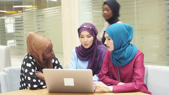 Thumbnail for Muslim Asian and African Women in Hijabs Sit in Cafes and Make Online Purchases Using a Laptop