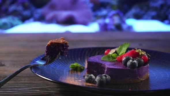 Thumbnail for Piece of Purple Cheesecake on Fork Near Aquarium.