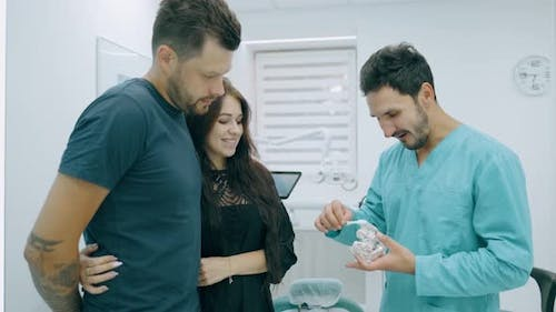 Doctor Dentist Is Showing To Happy Family on a Jaw Model How To Clean the Teeth with Toothbrush