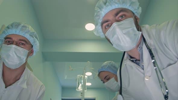 Группа хирургов, глядя вниз на пациента по пути к операционной комнате