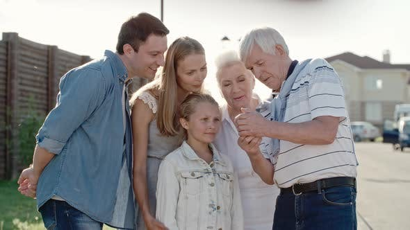 Thumbnail for Elderly Man Showing Something on Smartphone to Family