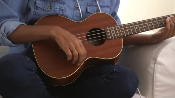 Thumbnail for Close up of girl strumming ukulele