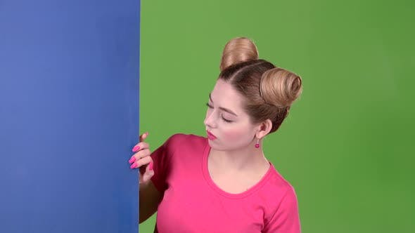 Thumbnail for Girl Peeks Out From Behind a Blue Board and Shows a Ok. Green Screen