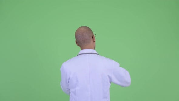 Thumbnail for Rear View of Bald Multi Ethnic Man Doctor Pointing Finger