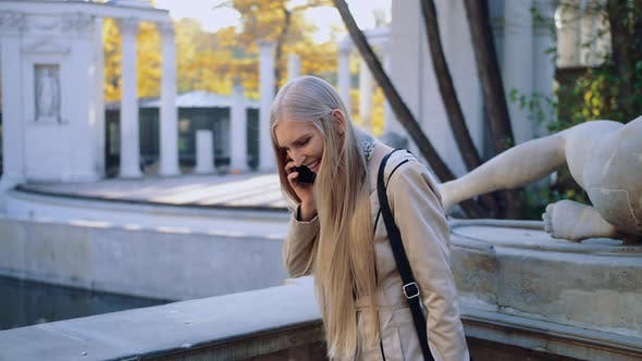 Thumbnail for A Happy Young Girl Is Talking on a Mobile Phone in the Autumn Park of the City