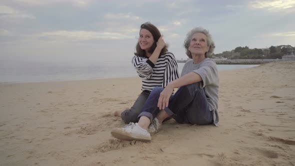 Thumbnail for Happy Old Mother Hugging and Kissing Beautiful Adult Daughter on Sand Near Sea