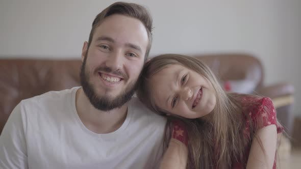 Thumbnail for Portrait of Handsome Bearded Man and Cute Positive Girl Looking in the Camera Smiling. The Child