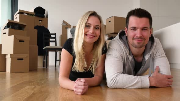 Thumbnail for A Happy Moving Couple Lies on the Floor of an Empty Apartment and Smiles at the Camera