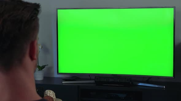 A Man, the Back of His Head To the Camera, Watches a TV with a Green Screen
