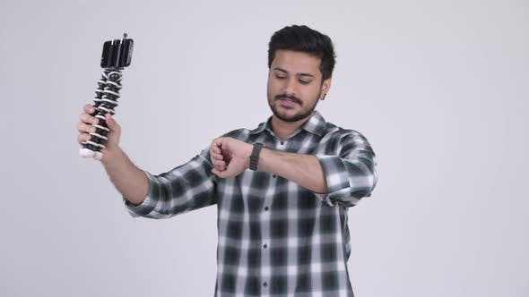 Cover Image for Portrait of Young Happy Bearded Indian Man Vlogging with Phone