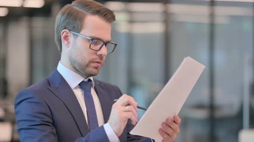 Portrait of Businessman Reading Documents in Office