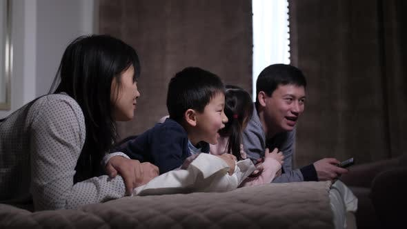 Thumbnail for Joyful Asian Family with Kids Watching Film on TV