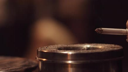 Thumbnail for Woman drops ash of a cigarette into the ashtray, beautiful wisp of smoke
