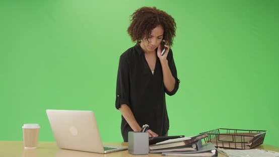 Thumbnail for Young black woman listens to a phone call and looks at her pad on green screen
