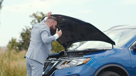Nervous Businessman Looking at Opened Hood and Trying To Fix Problem, Standing in Countryside