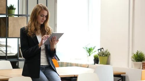 Browsing Online on Tablet by Businesswoman Sitting on Desk