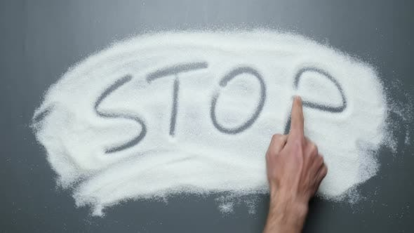 Hand writes word stop on sugar. Stop diabetes. Cancer and obesity diseases.