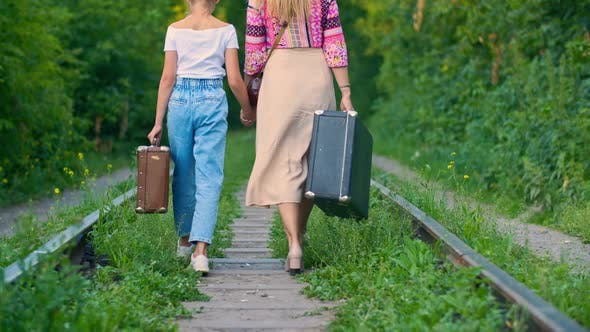 Thumbnail for Mom and Daughter Holding Hands Walking on Old Railroad with Vintage Suitcase. Back View Mother and