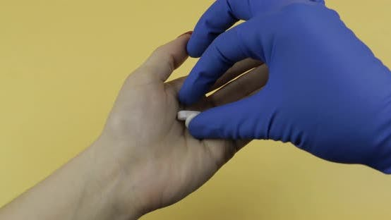 Thumbnail for Hand Dressed in Blue Medical Glove Puts Two White Pill Into Woman Hand