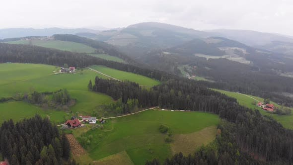 Thumbnail for Flying Over a Small Village on the Austrian Green Hills in Foggy Weather