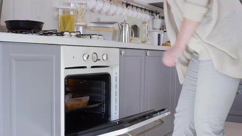 Frau nehmen Kuchen aus dem Ofen