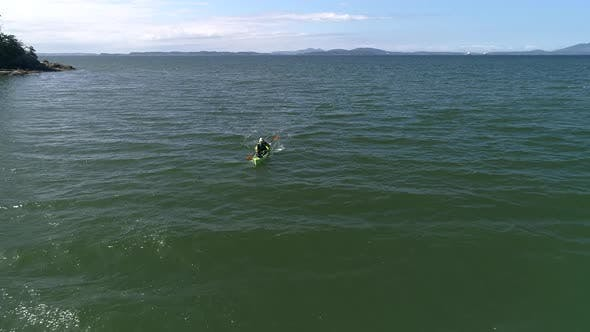 Thumbnail for Drone Flying Backwards Facing Man Paddling Kayak In Green And Blue Ocean Water
