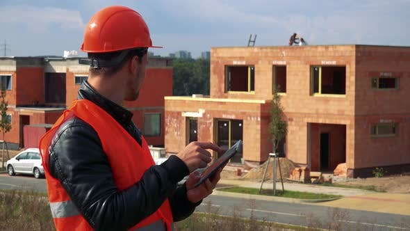Thumbnail for A Young Construction Worker Works on a Tablet, a House Under Construction in the Background
