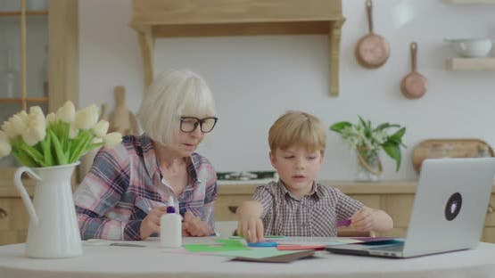 Preschooler Makes Art Homework with Glue, Scissors and Color Paper and Shows His Artwork To Laptop